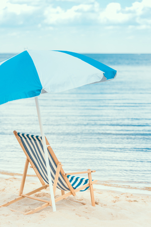 blue sun umbrella and beach chair on seaside in summer 스톡 콘텐츠