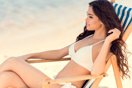 attractive brunette woman resting on beach chaise longue