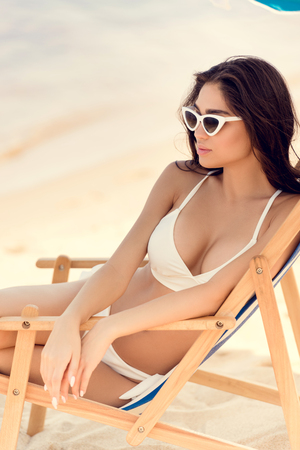 attractive young woman in sunglasses sitting on beach chair Stock Photo
