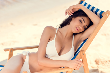 attractive brunette woman relaxing on beach chair Stock Photo
