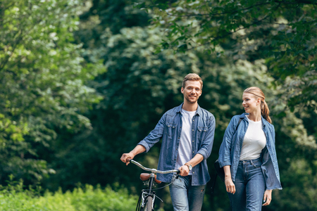 smiling young couple walking by park with vintage bicycle