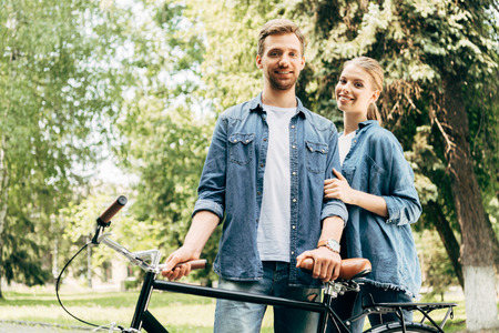 beautiful young couple with vintage bicycle standing at park and looking at camera