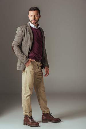 bearded man posing in stylish autumn tweed jacket, on grey