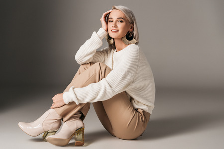 elegant fashionable woman posing in white sweater and autumn heels, on grey