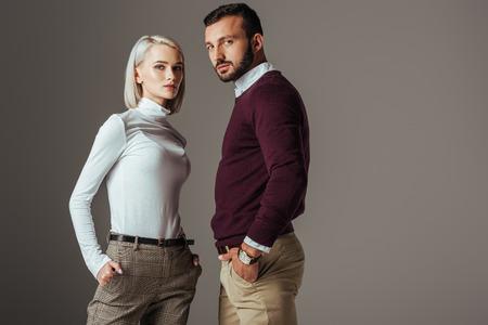 Paar posiert im modischen Herbstoutfit, isoliert auf grau