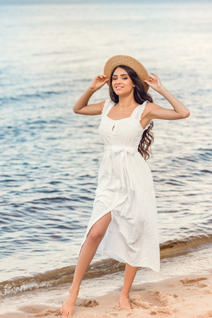 attractive smiling woman in straw hat and white dress walking on seashore