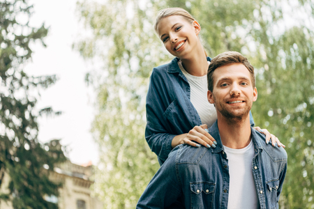 beautiful young woman piggybacking on her boyfriend at park and looking at camera Stock Photo