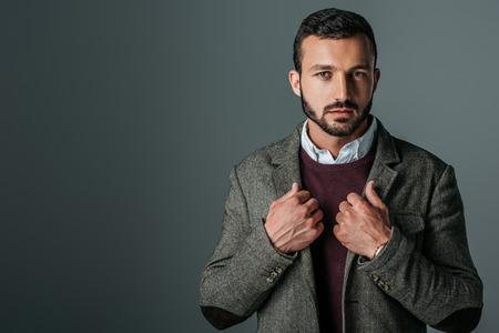 handsome stylish man posing in trendy tweed jacket, isolated on grey