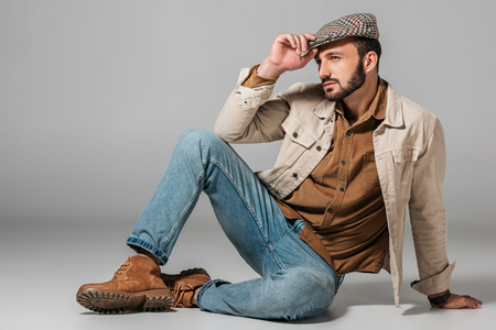 handsome man posing in corduroy shirt and autumn tweed cap, on grey