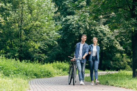 happy young couple walking by park with vintage bicycle