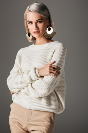 attractive girl posing in white knitted sweater and round earrings, isolated on grey Zdjęcie Seryjne