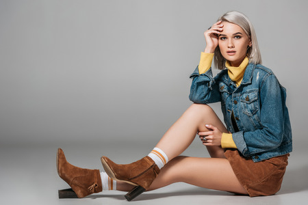 beautiful model in trendy corduroy skirt and jeans jacket sitting on floor, on grey