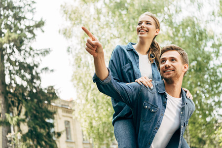 beautiful young woman piggybacking on her boyfriend while he pointing somewhere at park Stock Photo
