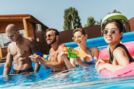 smiling multicultural friends having fun with water guns in swimming pool Stok Fotoğraf