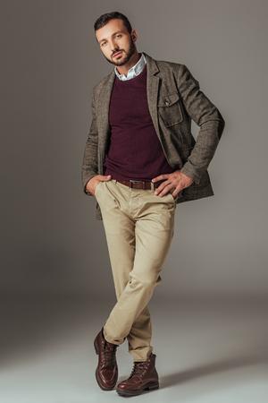 handsome stylish man posing in autumn tweed jacket, on grey