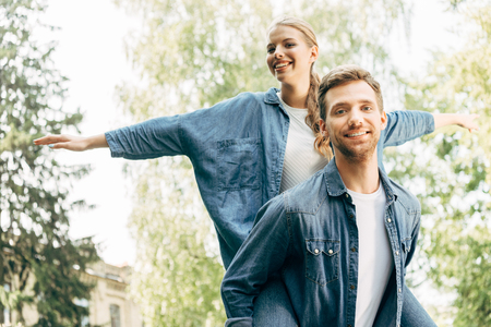 smiling young woman piggybacking on her boyfriend at park