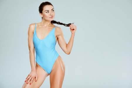 sexy sportive woman in blue swimwear touching ponytail isolated on grey
