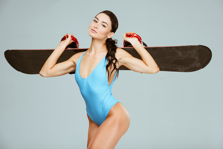 sexy snowboarder in blue swimsuit holding snowboard on shoulders isolated on grey Stock Photo