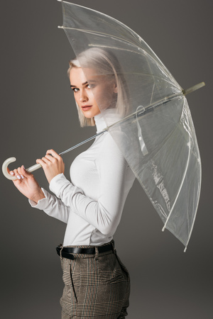 attractive blonde woman in autumn turtleneck posing with transparent umbrella, isolated on grey Stock Photo