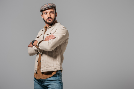 handsome man in autumn jacket and tweed cap posing with crossed arms, isolated on grey