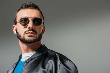 bearded man posing in black bomber and sunglasses,  isolated on grey Banco de Imagens