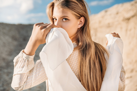 beautiful blonde girl with white scarf walking on sand dune Фото со стока