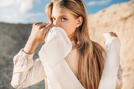 beautiful blonde girl with white scarf walking on sand dune Foto de archivo
