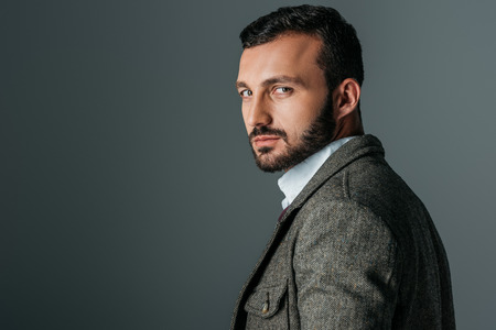 handsome confident man posing in tweed jacket, isolated on grey Stock Photo