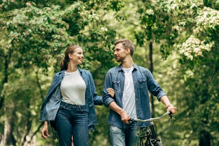 happy young couple in denim shirts with bicycle walking by park 스톡 콘텐츠 - 108001388