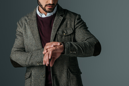 cropped view of bearded man in tweed jacket looking at watch, isolated on grey