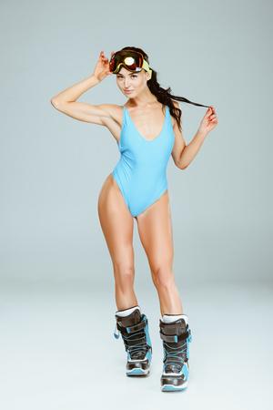 Sportlerin in blauer Badebekleidung und Skischuhen isoliert auf grau Standard-Bild
