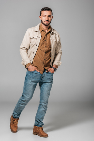 handsome man posing in corduroy shirt and autumn jacket with hands in pockets of jeans, on grey Stock Photo