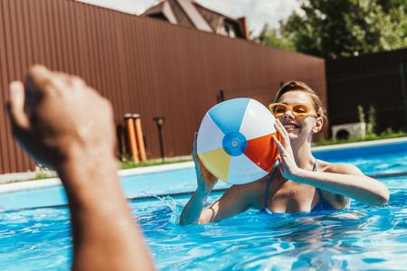 happy woman playing with beach ball in swimming pool 版權商用圖片