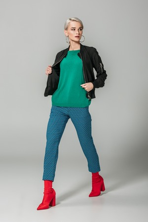 stylish female model in black jacket and red boots posing on grey background