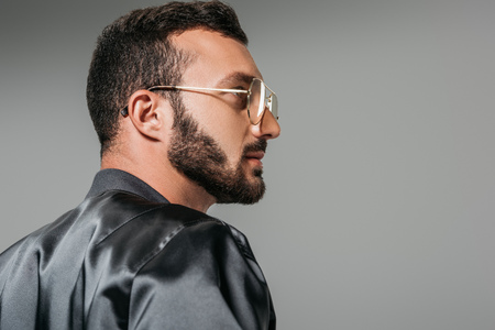 side view of bearded man in stylish eyeglasses and black bomber isolated on grey background