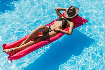 young woman in black swimsuit and straw hat sunbathing on pink inflatable mattress in swimming pool