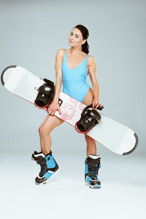 sexy sportswoman in blue sportswear holding snowboard isolated on grey Stock Photo