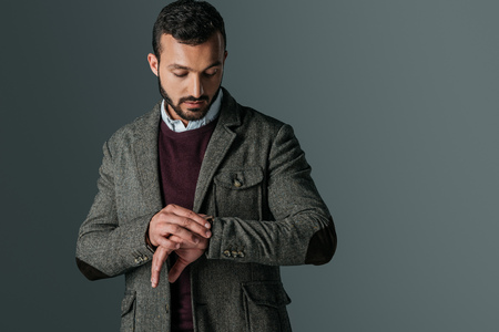 handsome man in tweed jacket looking at wristwatch, isolated on grey Stock Photo