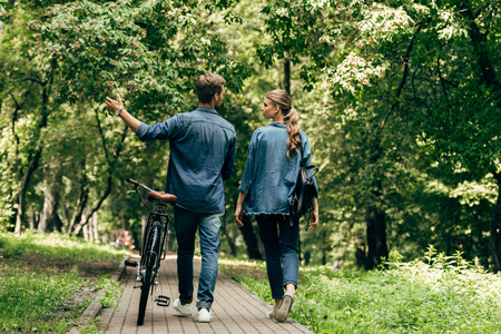 rear view of beautiful young couple in denim shirts with bicycle walking by park 스톡 콘텐츠