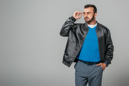 stylish male model adjusting eyeglasses and looking away isolated on grey background