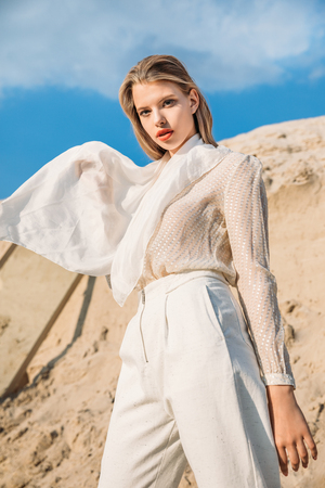attractive blonde model with white silk scarf posing in desert Stock Photo