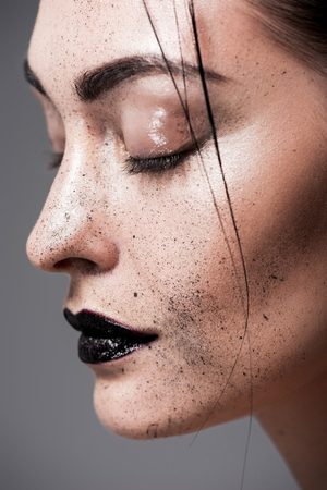 profile portrait of attractive model with black lips and freckles on face, isolated on grey