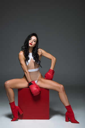 sexy athletic woman in white swimwear and boxing gloves sitting on red cube on grey