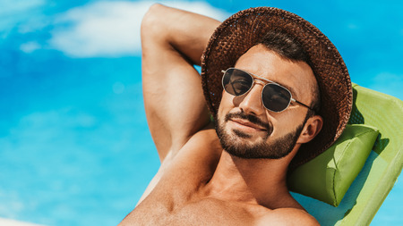 handsome man in sunglasses and straw hat sunbathing on sunbed at poolside