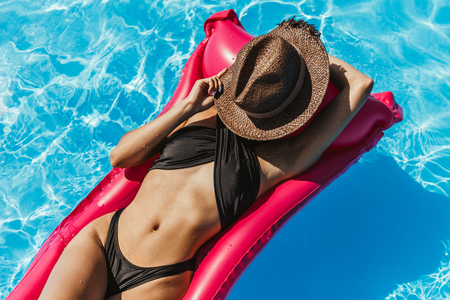 slim girl in swimsuit and straw hat sunbathing on inflatable mattress in swimming pool Stock fotó
