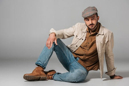 bearded man posing in corduroy shirt, jeans and autumn jacket and tweed cap, on grey