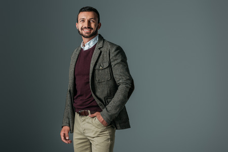 handsome smiling man posing in tweed jacket, isolated on grey Stock Photo