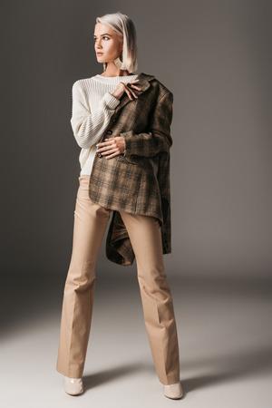 stylish elegant model posing in autumn sweater, beige pants and tweed jacket, on grey