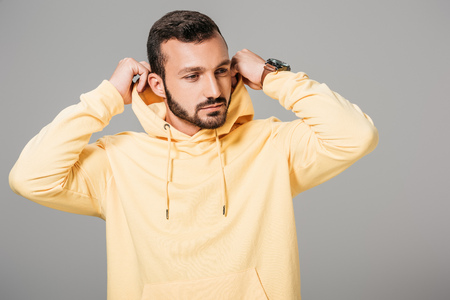 handsome bearded male model putting on yellow hoodie isolated on grey background