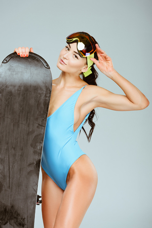 sexy sportswoman in blue leotard standing with snowboard and ski goggles isolated on grey Stock Photo